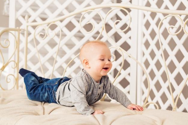 Śliczny roześmiany chłopczyk w słonecznej sypialni