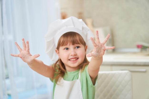 Śliczny roześmiany dziecko kucharz macha jego rękami