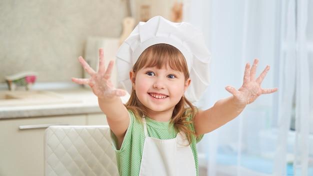 Śliczny roześmiany mała dziewczynka szef kuchni pokazuje jej palmy