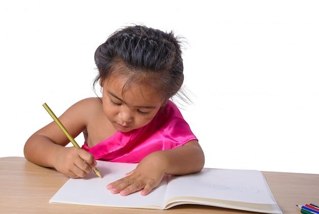 Śliczny rozochocony dziecka rysunek używać koloru ołówek podczas gdy siedzący przy stołem odizolowywającym na białym tle