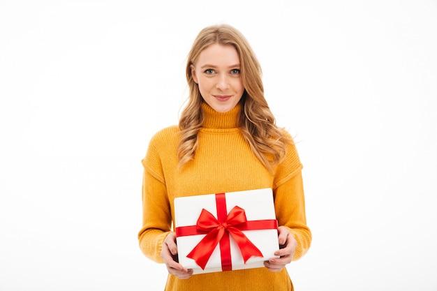 Śliczny rozochocony młodej kobiety mienia niespodzianki prezenta pudełko.