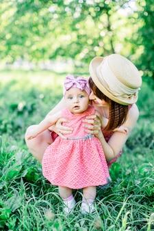 Śliczny śmieszny szczęśliwy dziecko robi jego pierwszym krokom na zielonej trawie, matka trzyma jej ręki wspiera uczenie się chodzić
