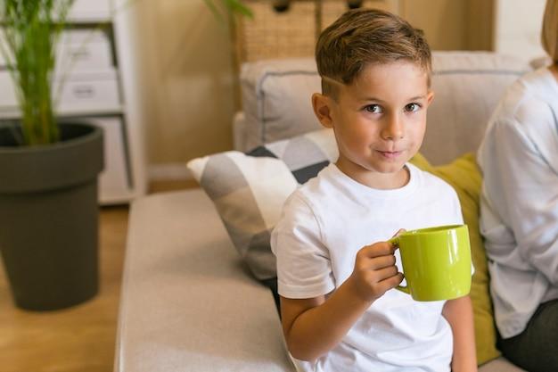 Śliczny smiley chłopiec trzyma żółtego kubek