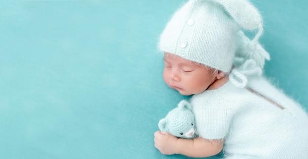 Śliczny śpiący noworodek w dzianinowym niebieskim garniturze