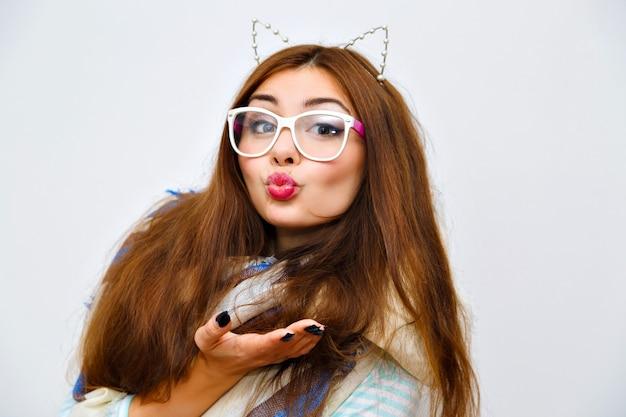 Śliczny styl życia portret młodej, ładnej brunetki z niesamowitymi długimi włosami, jasnym, świeżym makijażem, zabawą i szalonym gongiem, zimą, przytulnym ciepłym szalikiem, modnymi okularami i akcesoriami.