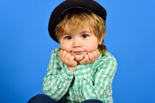 Śliczny stylowy chłopak w kraciastej koszuli i aksamitnej czapce trzyma twarz na rękach modny portret zbliżenie