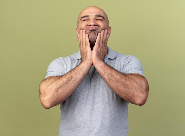 Śliczny, swobodny mężczyzna w średnim wieku trzymający ręce na policzkach, ściskający usta z zamkniętymi oczami odizolowanymi na oliwkowozielonej ścianie