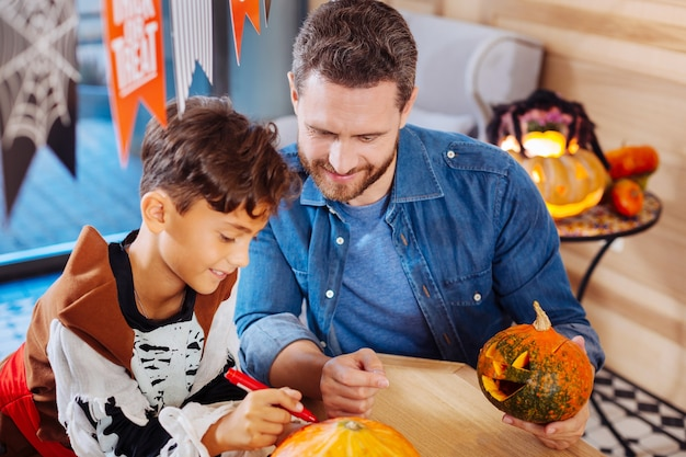 Śliczny syn. widok z góry promieniejącego uroczego syna i kochającego ojca, kolorującego dynie na rodzinne uroczystości halloween