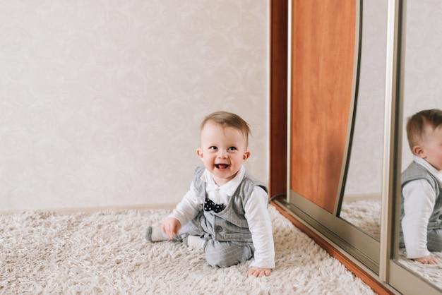 Śliczny szczęśliwy dziecko w eleganckim dżentelmenu kostiumu obsiadaniu na białym tle ono uśmiecha się i śmia się