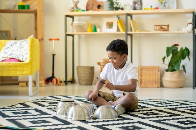 Śliczny szczęśliwy mały chłopiec w wieku podstawowym siedzi na podłodze salonu i bije na blaty metalowych misek w środowisku domowym