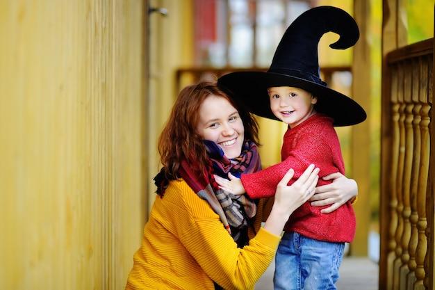 Śliczny szczęśliwy mały czarownik i jego młoda matka outdoors