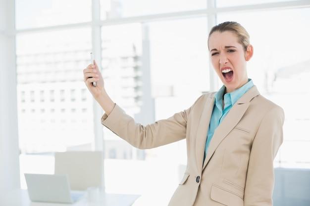 Śliczny szokujący bizneswoman trzyma jej smartphone patrzeje kamerę