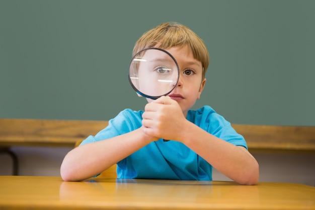 Śliczny uczeń ono uśmiecha się przy kamerą w sala lekcyjnej mienia powiększać - szkło