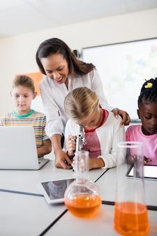 Śliczny uczeń patrzeje przez mikroskopu z nauczycielem