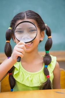 Śliczny uczeń patrzeje przez powiększać - szkło w sala lekcyjnej