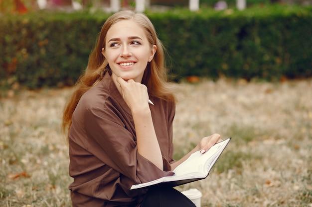 Śliczny uczeń pracuje w parku i używa notatnika