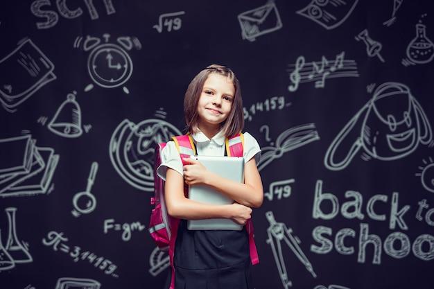 Śliczny uczeń przygotowuje się do pójścia do szkoły z plecakiem i tabletem w rękach z powrotem do koncepcji szkoły