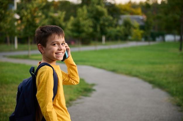 Śliczny uczeń ubrany w żółtą bluzę z plecakiem rozmawiający przez telefon komórkowy w publicznym parku, wracający do domu po szkole, uśmiechający się z ząbkowanym uśmiechem do kamery