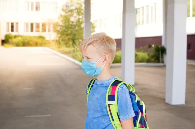 Śliczny uczeń z maską ochronną i plecakiem
