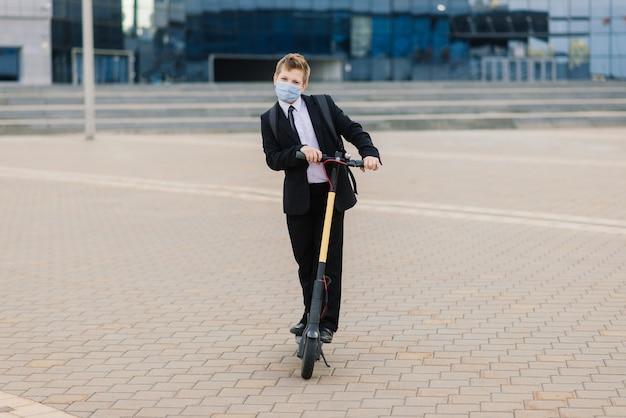 Śliczny uczeń z maską ochronną prowadzący skuter po mieście.