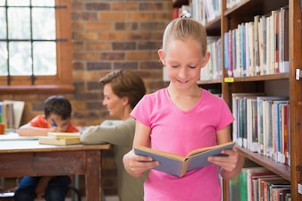 Śliczny ucznia czytanie w bibliotece