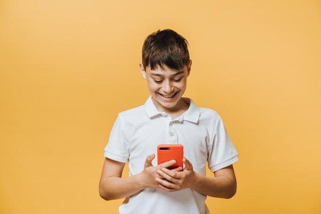 Śliczny uczniak w białej koszulce wykonujący rozmowę wideo ze swoim przyjacielem podczas kwarantanny, uśmiechnięty szeroko, szczęśliwy, że łączy go cały świat dzięki technologiom internetowym.