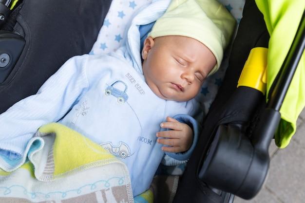 Śliczny uroczy chłopczyk leży w wózku na ulicy podczas spaceru zasnął z jedną ręką uniesioną do góry, palcami jednej ręki.