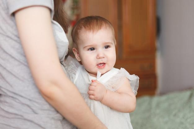 Śliczny uroczy noworodek w wieku 3 miesięcy z pieluchami. hapy mała dziewczynka lub chłopiec patrząc w kamerę i białą sukienkę. sucha i zdrowa koncepcja ciała i skóry dla dzieci. przedszkole dla niemowląt