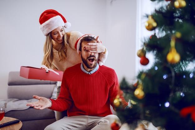 Śliczny uśmiechnięty caucasian kobiety mienia prezent i nakrycie jej chłopaka oczy. obie mają czapki mikołaja na głowach. na pierwszym planie jest choinka. wnętrze salonu.