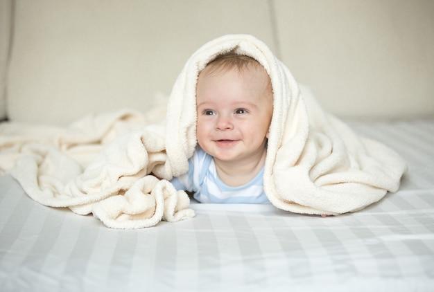 Śliczny uśmiechnięty chłopczyk leżący na łóżku pod białym kocem