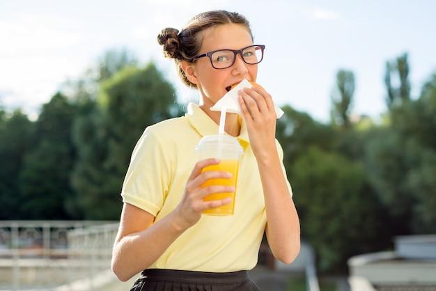 Śliczny uśmiechnięty nastolatek trzyma sok pomarańczowego i hamburger.