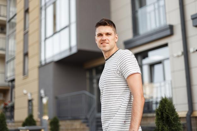 Śliczny wesoły młody człowiek w klasycznej koszulce w paski ze stylową fryzurą z pięknym uśmiechem spaceruje po ulicach miasta.