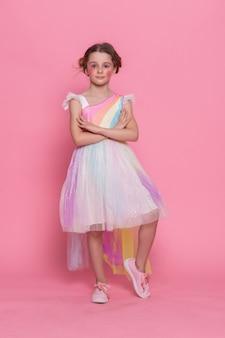 Śliczny widok szczęśliwej małej dziewczynki noszącej opaskę jednorożca z różową ścianą jako tło. portret słodkie uśmiechnięte dziecko z rogiem jednorożca i uszami stojąc na chodniku. urocze dzieciaki w kostiumach