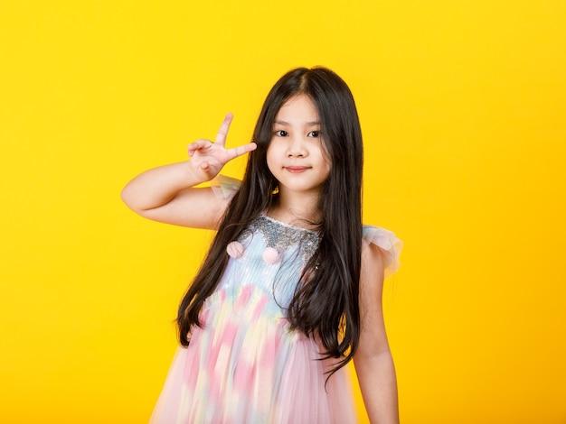 Śliczny wycięcie portret młodej ładnej azjatyckiej dziewczyny na uroczej, casualowej sukience wykonaj atrakcyjny gest palcem jako pewny siebie znak zwycięstwa z wesołą twarzą, aby żywy wyrazić pewny sukces, gwarancja spełniona