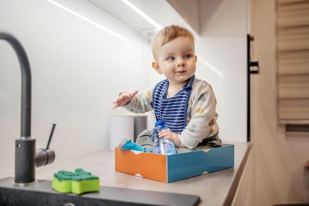 Śliczny zabawny kaukaski blond chłopiec siedzi w pudełku na blacie kuchennym i bawi się tak, jakby był w pociągu.
