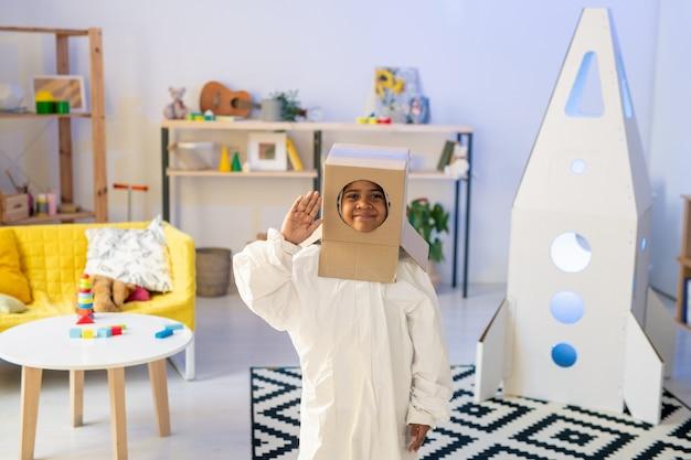 Śliczny zabawny kosmonauta w białych ubraniach i tekturowym pudełku na głowie trzymający prawą rękę przy skroni podczas zabawy w salonie