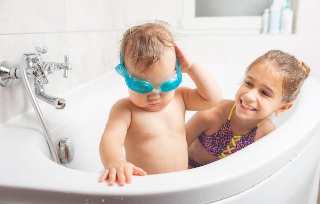 Śliczny zabawny mały chłopiec w niebieskich okularach pływackich stoi w łazience obok swojej starszej siostry