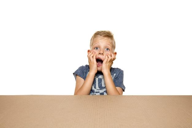 Śliczny, zdumiony chłopczyk otwierający największą paczkę pocztową.