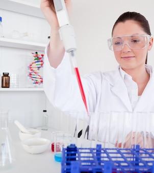 Śliczny żeński biolog trzyma ręczną pipetę z próbką od próbnych tubek