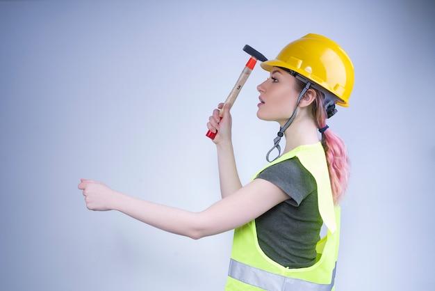 Śliczny żeński pracownik próbuje młotkować gwóźdź w ścianę