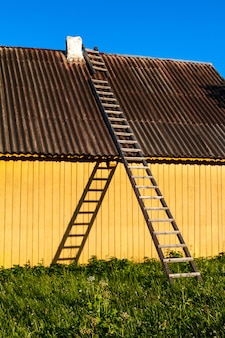 Śliczny żółty wiejski dom z drewnianymi schodkami w wsi.