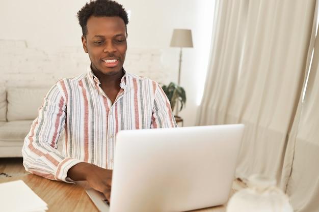 Śliczny, zrelaksowany młody afrykański mężczyzna siedzi przy użyciu zwykłego komputera przenośnego do rozmów z przyjaciółmi, grając w gry wideo online, mając szczęśliwy wygląd