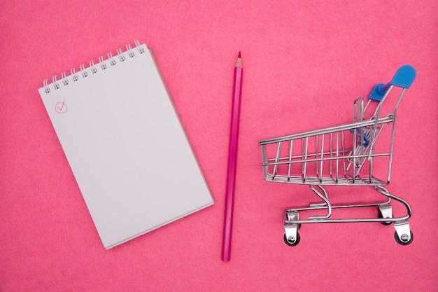 Ślimakowaty notepad na jaskrawym różowym tle. pojęcie nauki, rejestrowania ważnych informacji, dnia wiedzy, biznesu, notatek. leżał płasko, minimalizm, widok z góry. skopiuj miejsce