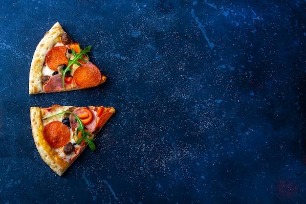 Slises świeżo przygotowanej pizzy pepperoni z salami, pomidorami i serem na ciemnym tle. tradycyjny włoski obiad lub kolacja. koncepcja fast food i street food. leżał płasko,