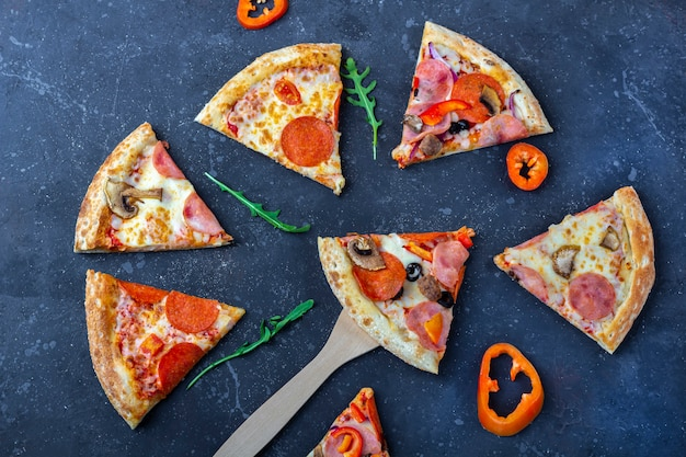 Slises świeżo przygotowanej pizzy z salami, pieczarkami, szynką i serem na ciemnym tle. tradycyjny włoski obiad lub kolacja. koncepcja fast food i street food. leżał płasko, kopiowanie miejsca na tekst