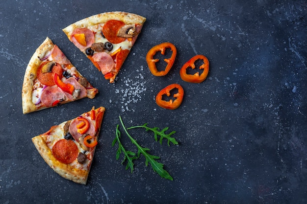 Slises świeżo przygotowanej pizzy z salami, pieczarkami, szynką i serem na ciemnym tle. tradycyjny włoski obiad lub kolacja. koncepcja fast food i street food. leżał płasko,