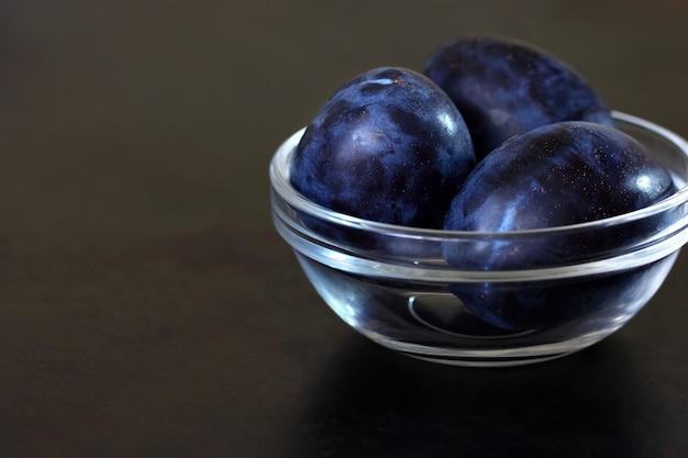 Śliwki niebieskie śliwki w szklanej misce na ciemnym blacie.
