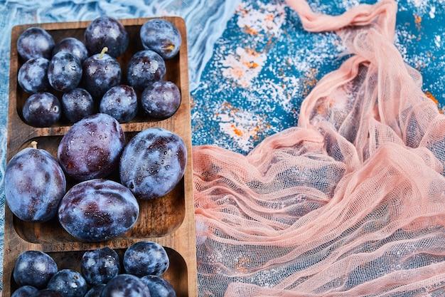 Śliwki ogrodowe na drewnianym talerzu i na niebiesko z obrusami.