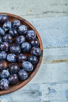 Śliwki ogrodowe na talerzu na niebiesko.
