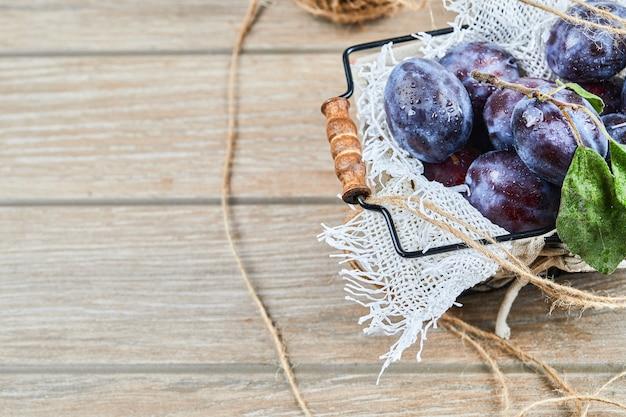 Śliwki ogrodowe w koszu na drewnianym stole. wysokiej jakości zdjęcie